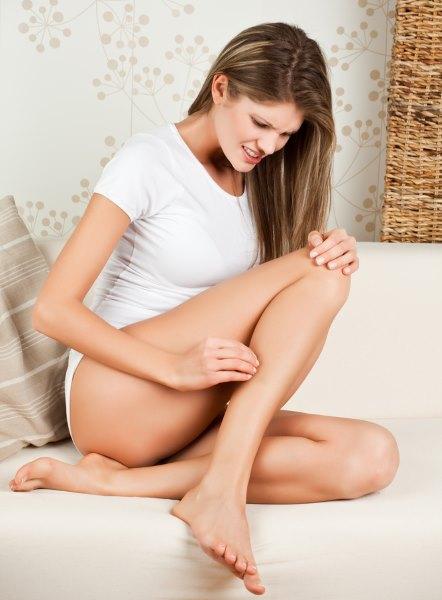 Девушка чешет ноги.