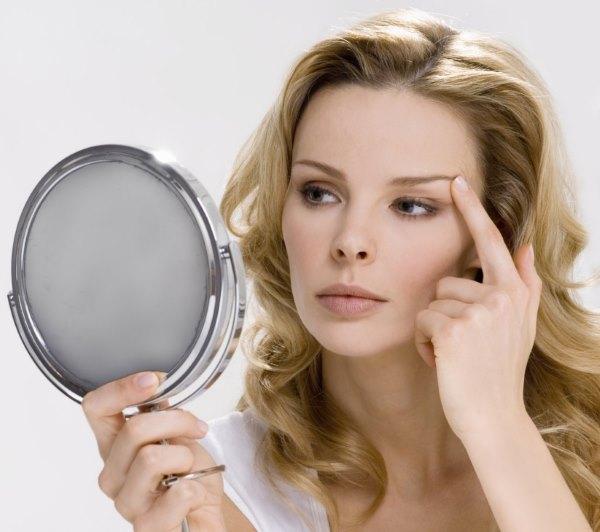 Девушка смотрит на себя в зеркало.