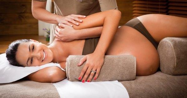 Бременной девушке делают массаж.