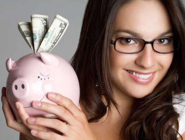 Девушка держит копилку с деньгами.