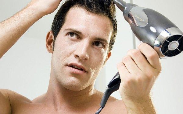 Мужчина сушит волосы феном.