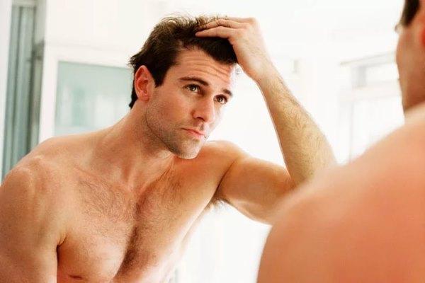 Мужчина смотрит на себя в зеркало.