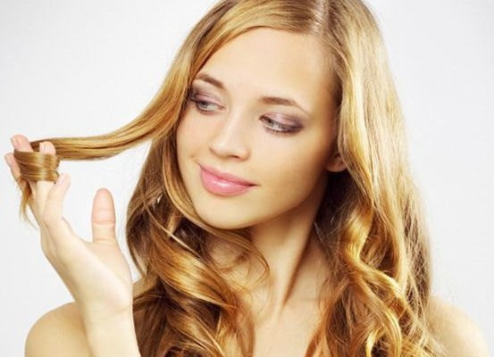 Девушка рассматривает свои волосы.