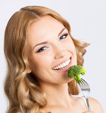 Девушка ест брокколи.