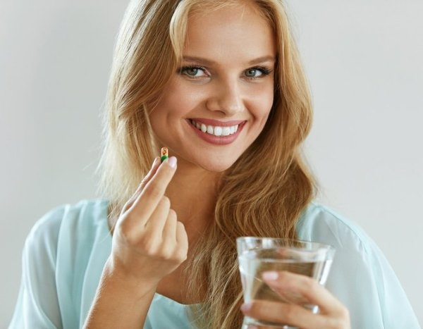 Девушка пьет витамины.